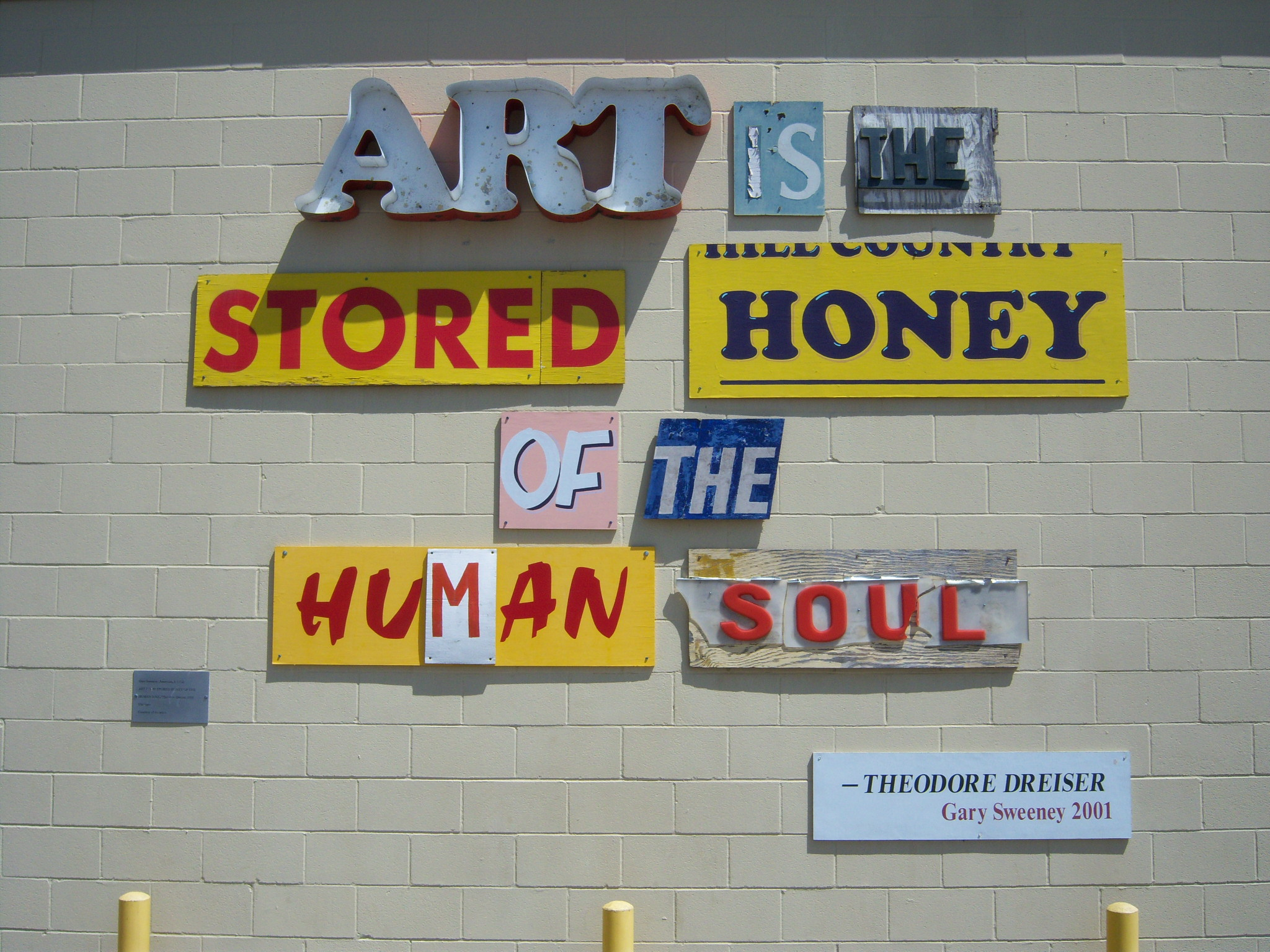 """Photo of artwork by Gary Sweeney outside of the San Antonio Museum of Art that reads """"Art is the stored honey of the human soul."""" (Quote by Theodore Dreiser.)"""