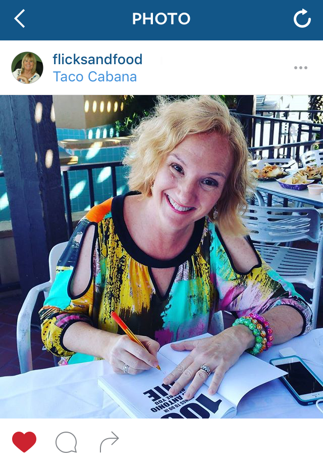 """Photo of Denise Richter, author of """"100 Things To Do in San Antonio Before You Die"""" signing her book at Taco Cabana."""